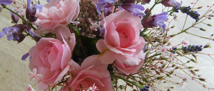 Ein Blumemstrauß mit rosa Rosen und blauen Blumen steht in ener Vase.