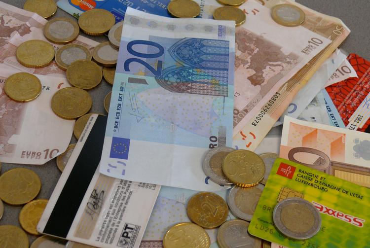 Scheine, Münzen und EC-Karten liegen auf einem Tisch.