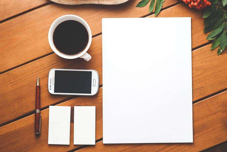 Eine Tasse Kaffee, ein Blatt Papier, ein Handy, zwei Post-its und ein Kugelschreiber liegen ordentlich ausgerichtet auf einem Tisch.