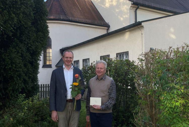 Pfarrvikar Ralph Regensburger (links) gratulierte vor der Kirche St. Ulrich im Pfarrverband Laim Diakon Georg Riepel zu seinem 15. Dienstjubiläum (Foto: priv.)
